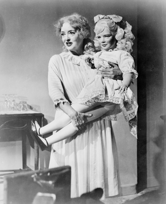 Full shot of Bette Davis as Jane Hudson holding large doll.