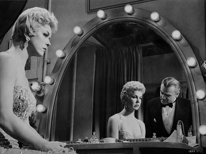 Doris Day sitting at vanity mirror with James Cagney wearing a tuxedo