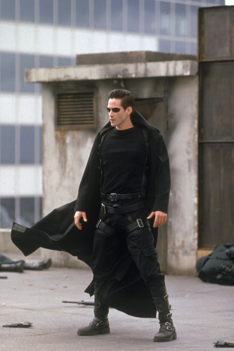 Full shot of Keanu Reeves as Thomas A. Anderson/Neo wearing sunglasses and coat/duster standing on skyscraper rooftop.