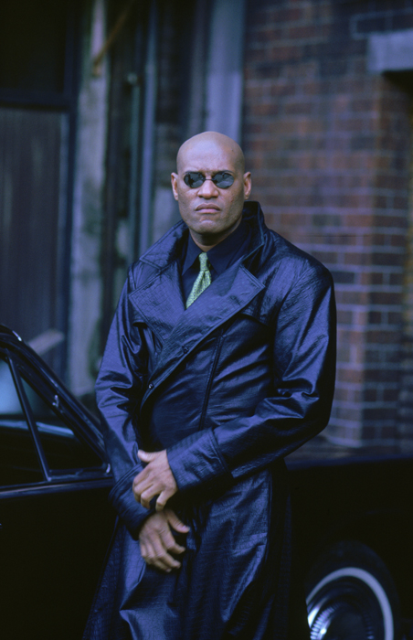 Full shot of Laurence Fishburne as Morpheus, wearing sunglasses and long leather coat.