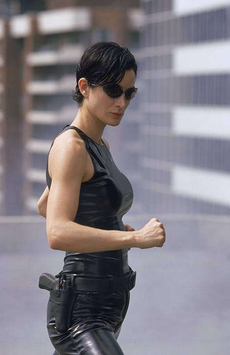 Medium shot of Carrie-Anne Moss as Trinity preparing to attack wearing sunglasses and gun in holster.