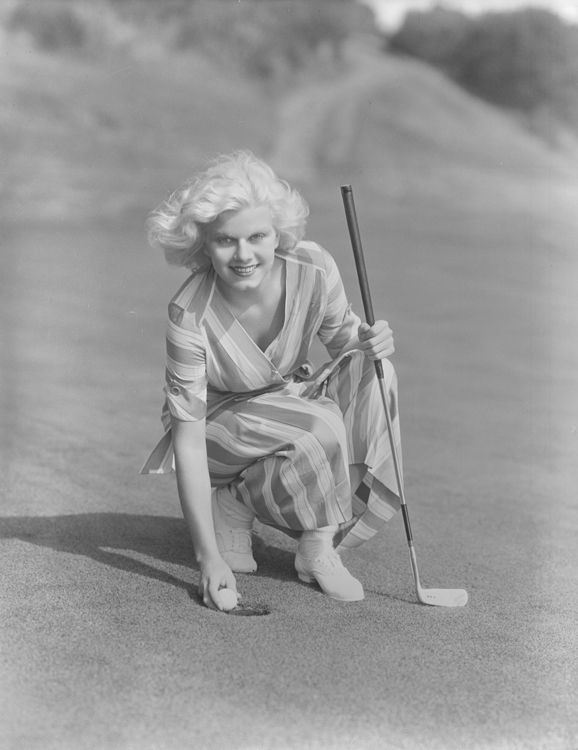 Full publicity shot of Jean Harlow on golf course holding club.