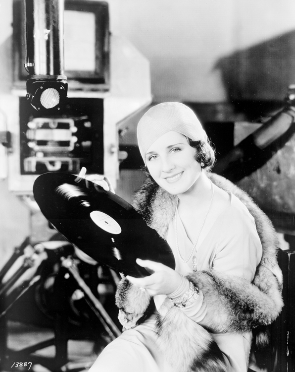 "Norma Shearer, 1929, holding over sized ""Sound on Disk"" album."