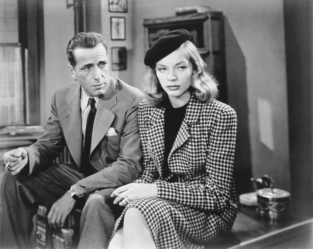 Humphrey Bogart as Phillip Marlowe and Lauren Bacall as Vivian Sternwood Rutledge, wearing hat/beret, both sitting on edge of desk and holding cigarette.