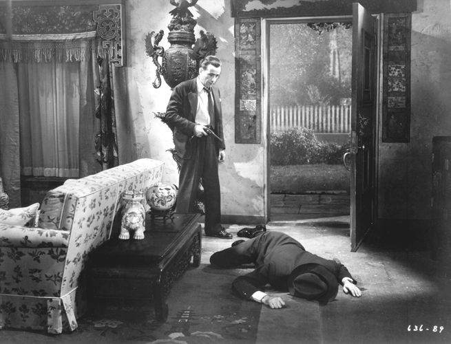 Humphrey Bogart as Phillip Marlowe, holding gun, standing over dead body of John Ridgely as Eddie Mars.