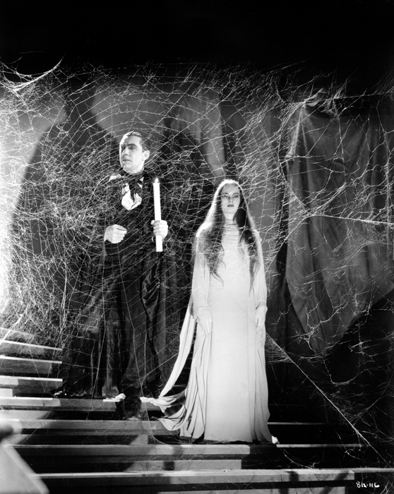 Bela Lugosi as Count Mora holding candle and Carroll Borland as Luna Mora, with large cobweb in front of them.