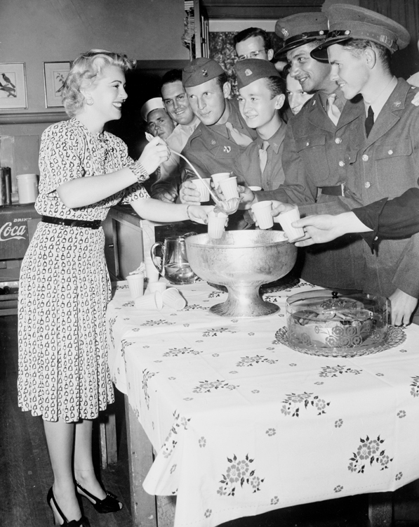Full shot of Lana Turner serving drinks from punch bowl to World War II Service men in uniform, 1942.