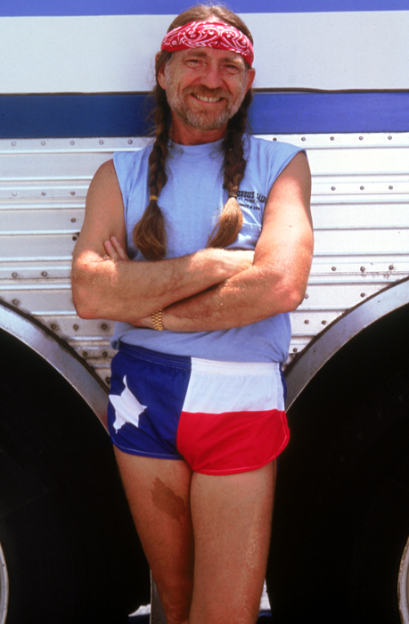 Willie Nelson as Buck, wearing headband/bandana, leaning against bus.