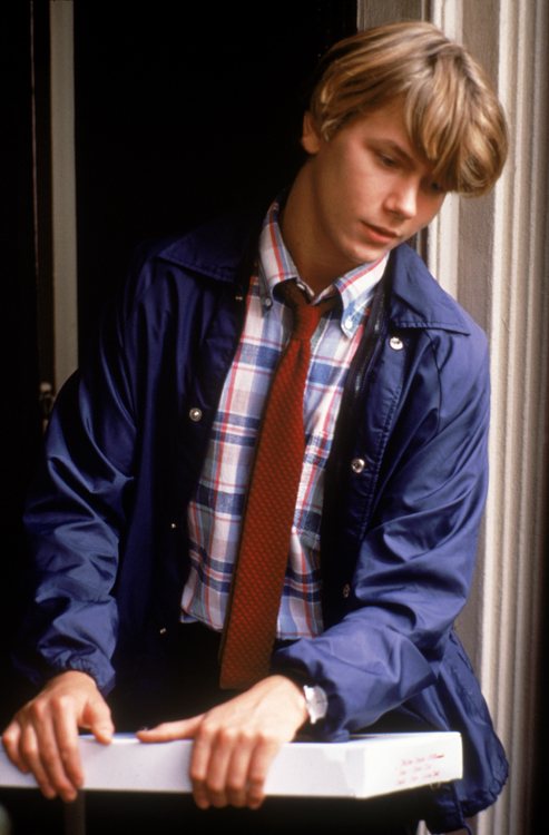 Medium shot of River Phoenix as Danny Pope, wearing tie, holding pizza box.