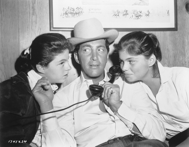 Medium BTS shot of Dean Martin as Bama Dillert, wearing cowboy hat, holding phone receiver, with daughters Gail (left) and Claudia Martin.