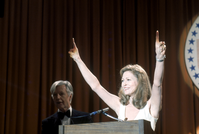 Faye Dunaway as Diana Christensen standing triumphant at podium.
