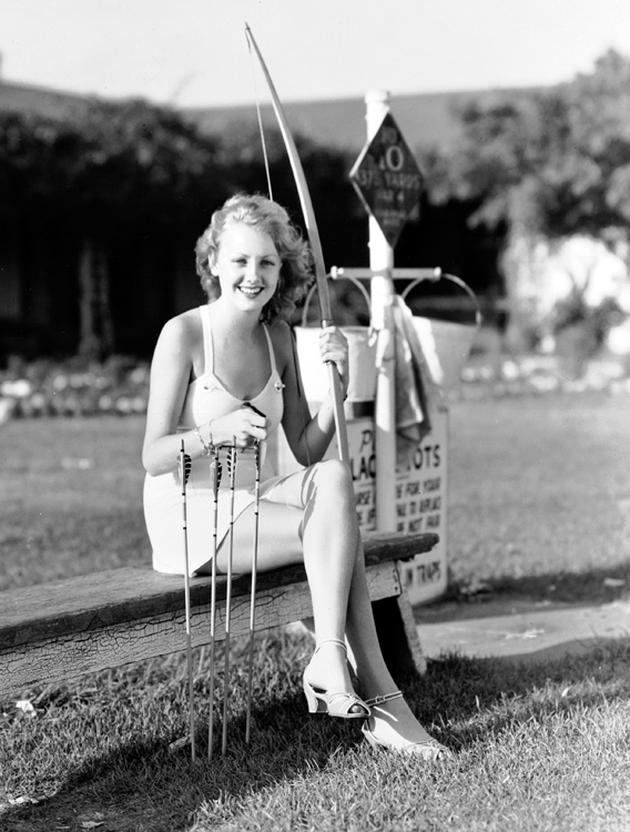 Virginia Grey during her first days at MGM, circa 1937. Photographed on location by Clarence Bull, she wears her sun suit, heels and appears to be learning about bow and arrow.