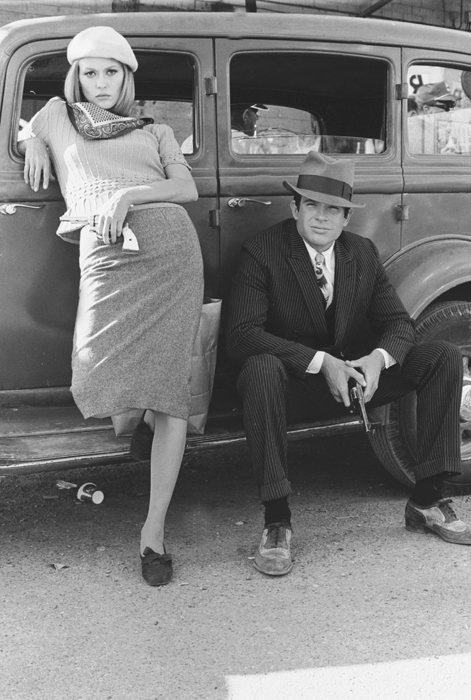 Faye Dunaway as Bonnie Parker and Warren Beatty as Clyde Barrow, wearing hat, both leaning on car and holding guns/pistols.
