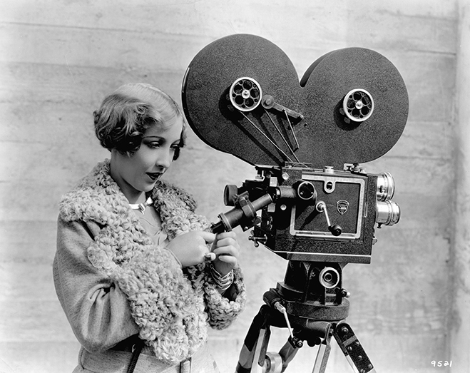 Bessie Love examining a part of a 35mm motion picture camera on a tripod