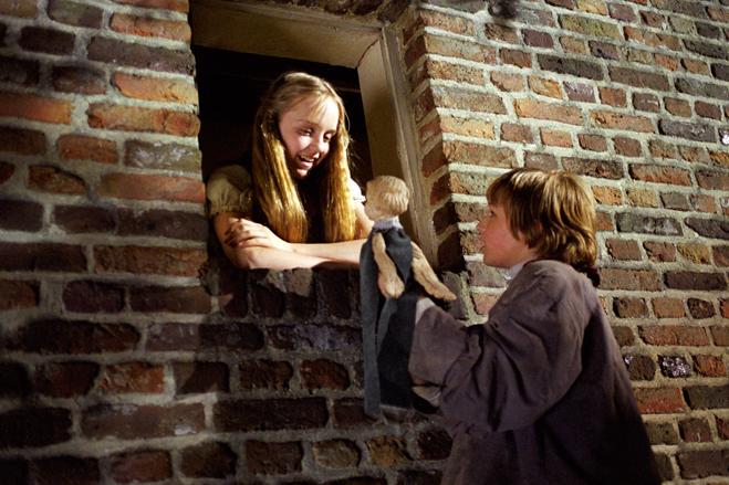 Farren Monet as Aloise, Jeremy James Kissner as Nello holding doll