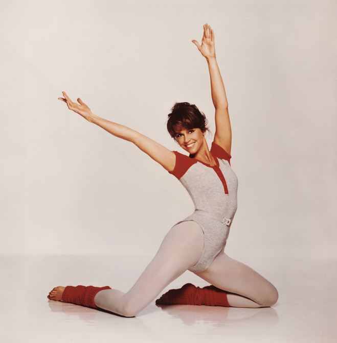 Jane Fond in leotard and leg warmers with arms upstretched