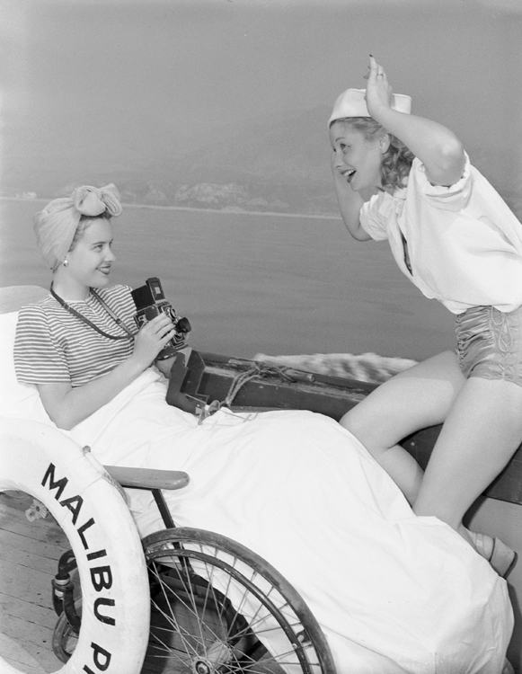 Susan Peters, seated in wheelchair, holding camera towards Lucille Ball, making funny face.
