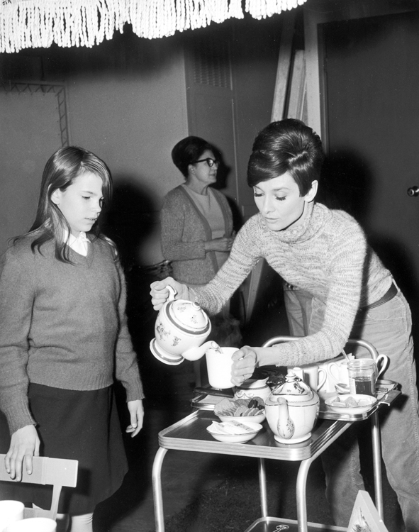 Behind-the-scenes shot of Audrey Hepburn as Susy Hendrix pouring tea for Julie Herrod as Gloria.