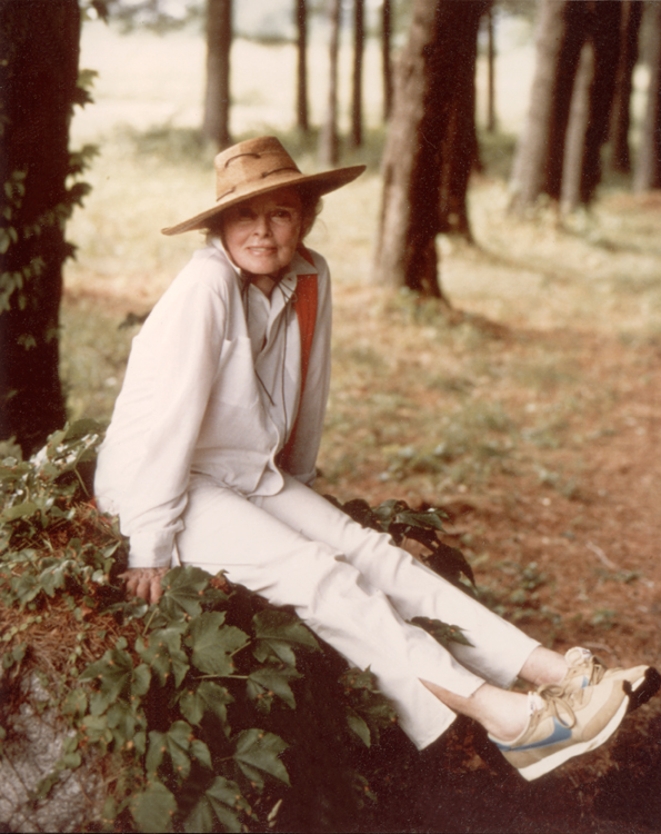 Katharine Hepburn wearing a large garden hat sitting outdoors