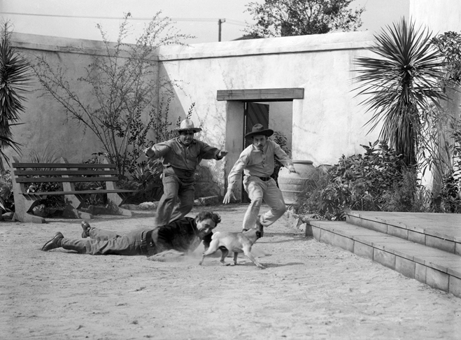 Spencer Tracy as Pilon lying on ground with Akim Tamiroff as Pablo with hat and John Qualen as Jose Maria Corcoran with hat running after dog.