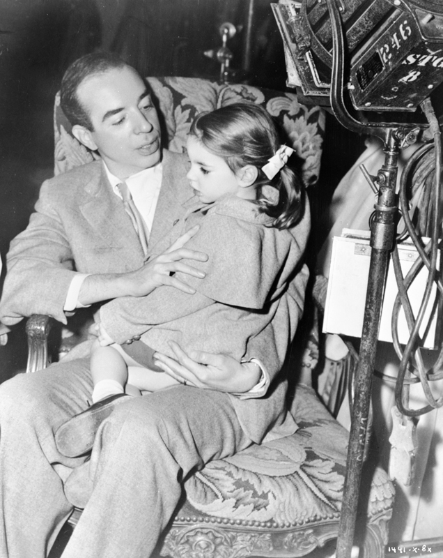 Medium BTS shot of director Vincente Minnelli seated with daughter Liza Minnelli on his lap.