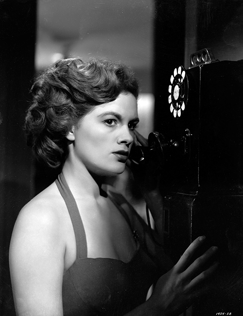 Medium shot of Jean Hagen as Harriette Sinton using pay phone.