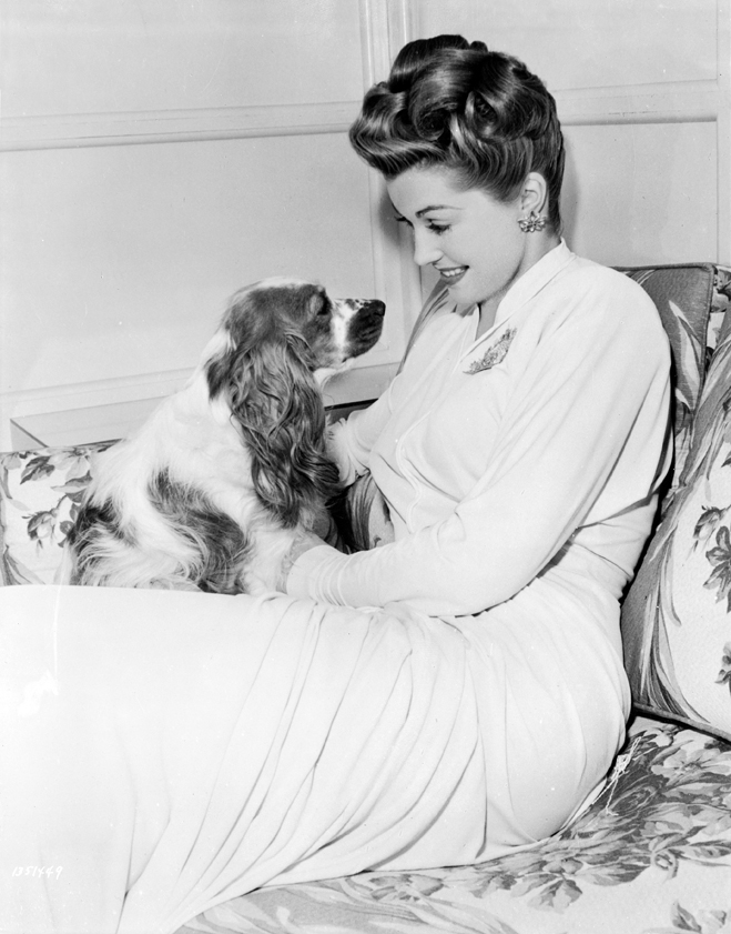 Esther Williams as Connie Allenbury sitting holding dog.