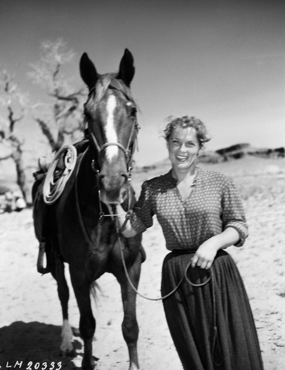 Denise Darcel in a behind-the-scenes photo with horse on the set of Westward the Women