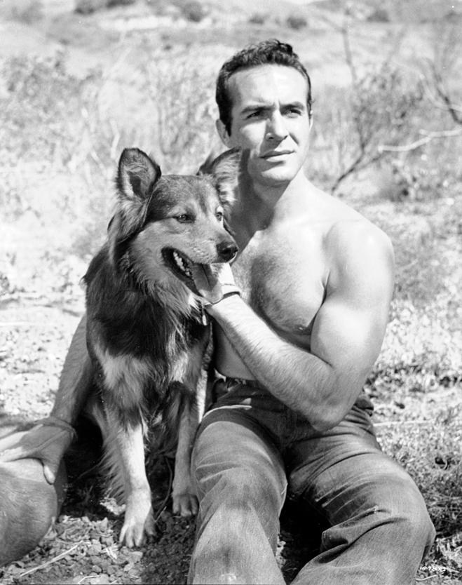 Ricardo Montalban as Chu Chu Ramirez seated on ground with dog.