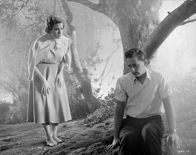 In woods of Deborah Kerr as Laura Reynolds looking at seated John Kerr as Tom Robinson Lee.