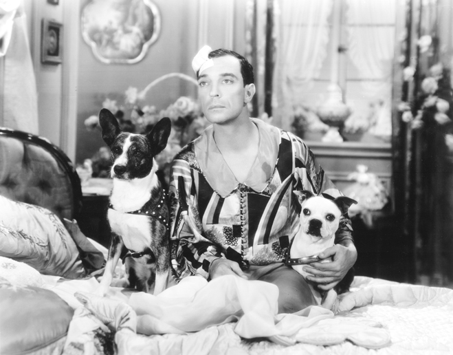 Medium shot of Buster Keaton as Reginald Irving seated on bed embracing two dogs.