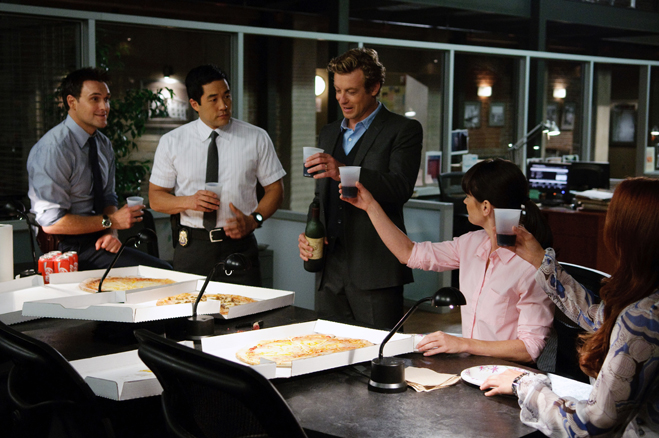 Medium shot of Owain Yeoman as Wayne, Tim Kang as Kimball, Simon Baker as Patrick Jane, standing, with Robin Tunney as Teresa Lisbon and Amanda Righetti as Grace, seated at table with boxes of pizza, toasting with plastic cups.