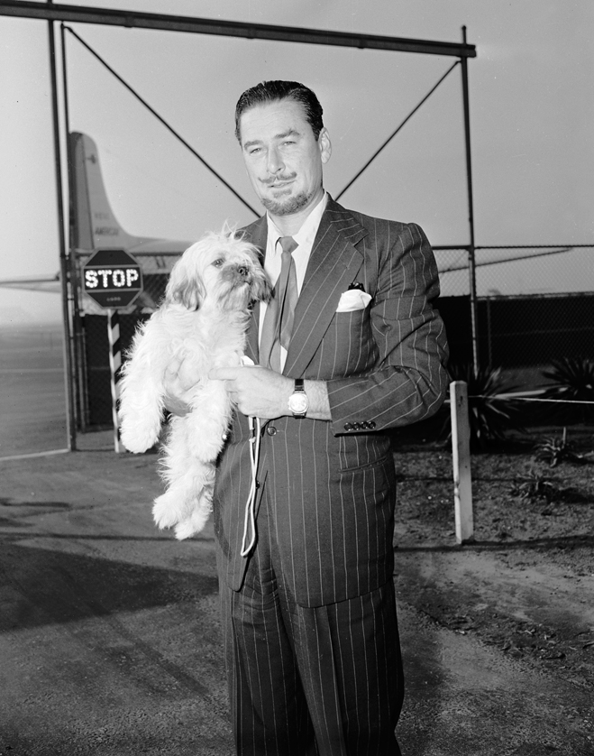 Erroll Flynn standing in an air field holding a Lhasa Apso dog
