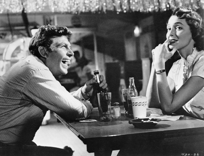 Andy Griffith as Lonesome Rhodes, laughing, seated at table in club with Patricia Neal as Marcia Jeffries.