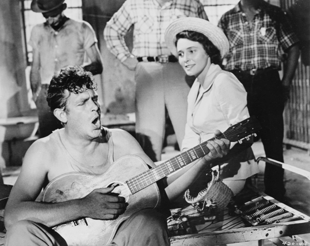 Medium shot in jail cell of Andy Griffith as Lonesome Rhodes, playing guitar and singing, while Patricia Neal as Marcia Jeffries, wearing hat, and men look on.
