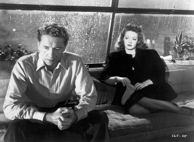 Paul Henreid as Karel Novak and Bette Davis as Christine Radcliffe, seated on couch