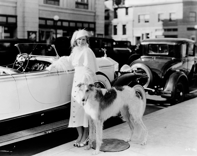 Jean Harlow with her Borzoi posing next to a convertible