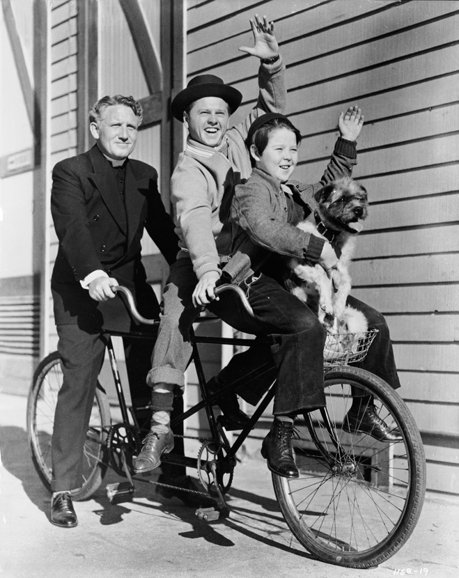 Behind the scenes shot, sitting on bicycle, of Spencer Tracy as Father Flanagan, Mickey Rooney as Whitey Marsh, wearing hat, and Bobs Watson as Pee Wee, holding dog.