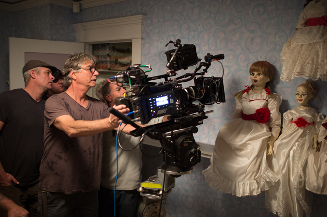 Behind the scenes shot of Annabelle sitting on a shelf with other dolls