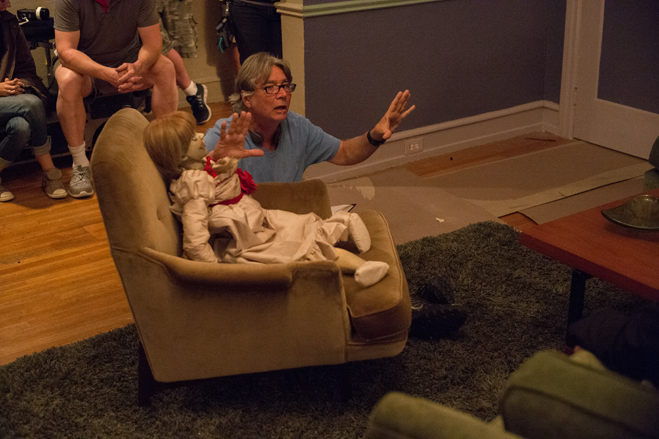 Annabelle sitting in an easy chair with director giving scene instructions