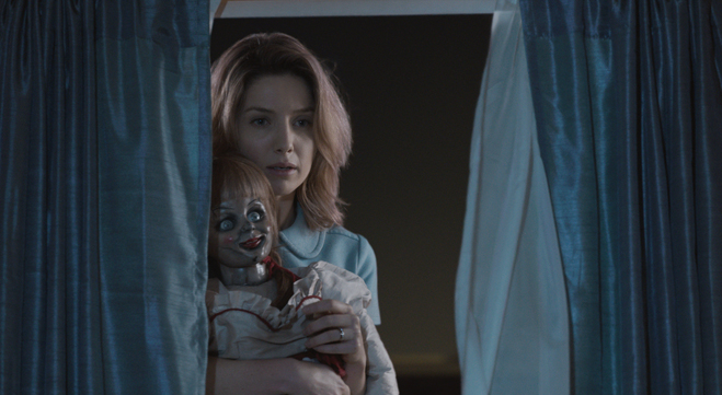 Annabelle Wallis as Mia looking out a window holding Annabelle the doll