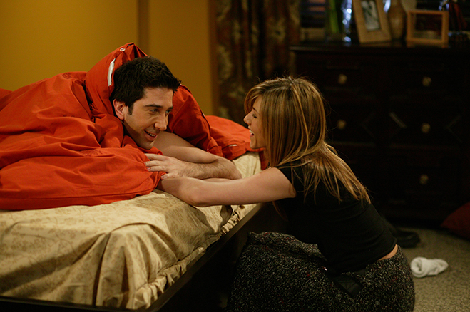 David Schwimmer and Jennifer Aniston as Ross and Rachel smiling at each other in Ross' bed