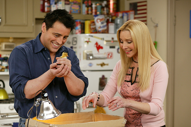 Medium shot of Matt LeBlanc as Joey holding baby duck and standing with Lisa Kudrow as Phoebe.