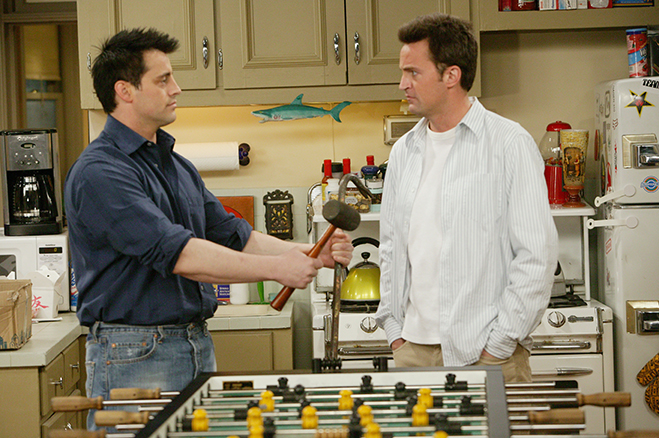 Medium shot of Matt LeBlanc as Joey holding hammer and standing near foosball table with Matthew Perry as Chandler.