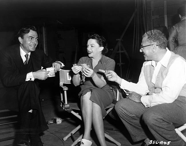 A Star is Born James Mason, Judy Garland, and director George Cukor between takes
