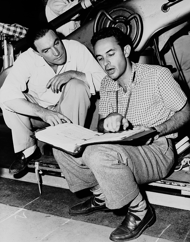 co-directors gene kelly and stanley donen go over the script on the set of singin' in the rain