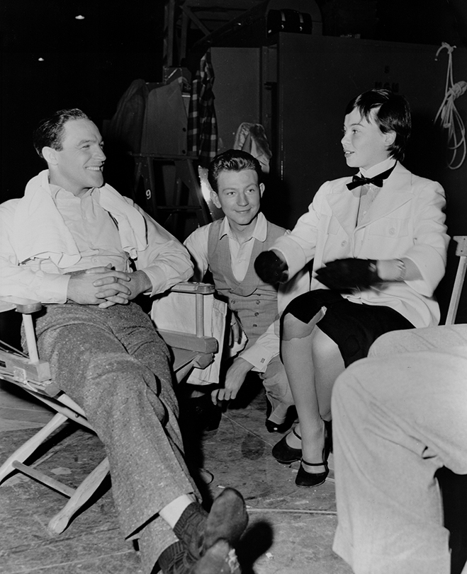 gene kelly and donald o'connor sit with visiting actress leslie caron on the set of singin' in the rain. caron was once considered for the starring role that went to the then-unknown debbie reynolds.