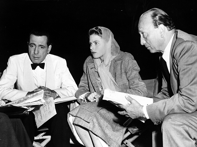 Humphrey Bogart, Ingrid Bergman and director Michael Curtiz going over the ongoing script on the set of Casablanca.