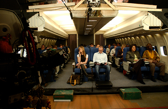 Wide BTS shot of Jennifer Aniston as Rachel sitting on airplane set with Jim Rash as Male Passenger.
