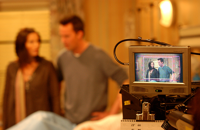 Medium BTS shot of Courteney Cox as Monica and Matthew Perry as Chandler visible in backgroud and on video monitor.